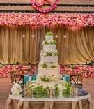 White wedding cake with white and green hydrangea in between each tier on a mirror tabletop