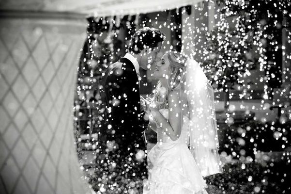 Black and white photo of bride and groom behind fountain