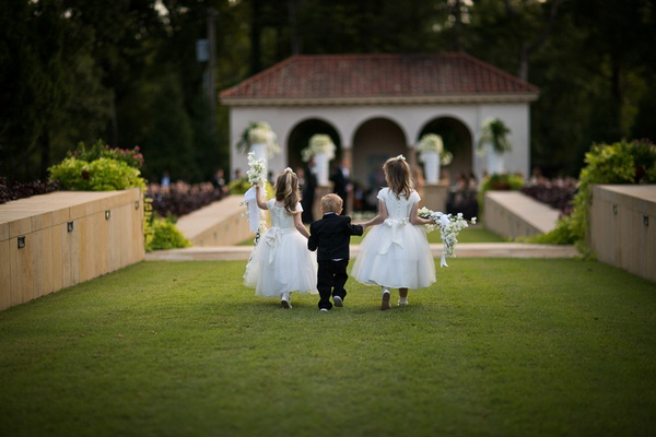 back view of two flower girls holding hands of toddler ring bearer in the middle