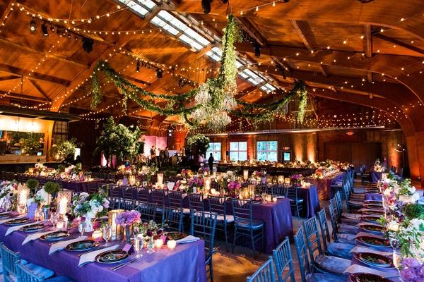 wedding reception barn purple linens low centerpieces pink purple candles twinkle lights garlands