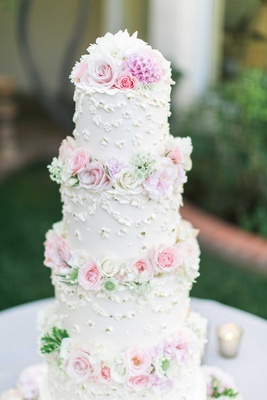 White four layer wedding cake with fresh pink and white roses in between layers