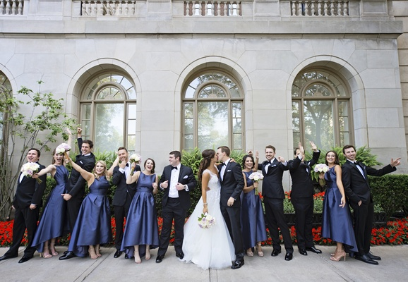 bride in hayley paige kisses groom in tuxedo, bridesmaids in alfred sung high-low satin navy dresses