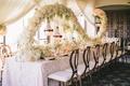 Long wedding reception table with swirl centerpiece of white hydrangeas, lilacs, stephanotis, tulips
