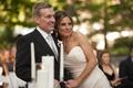 Bride in a strapless Romona Keveza gown and groom in a black tuxedo at outdoor ceremony