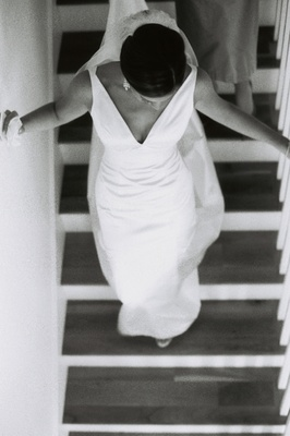 Black and white picture of bride walking down staircase wearing v-neck wedding dress