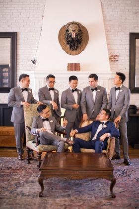 groomsmen in grey in lounge surrounding groom in navy sitting in vintage chair
