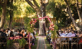 Outdoor bohemian wedding ceremony in tree grove with metal arch, peach, fuchsia red flowers, ribbons
