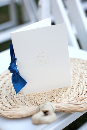 Simple white ceremony program with monogram and navy blue ribbon tie fold