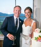 bride and groom pose wedding cake pink salmon flowers green sweetheart