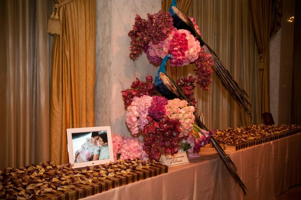 Wedding favors table with pink flowers and peacocks