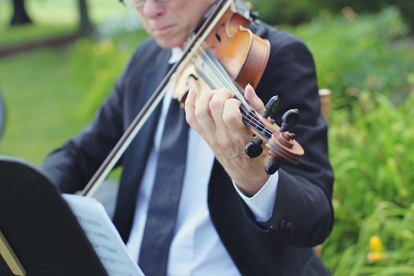 Man in navy suit on lawn using string instrument