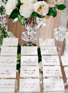 Calligraphy sophisticated escort cards place settings on mirror table at sophisticated wedding