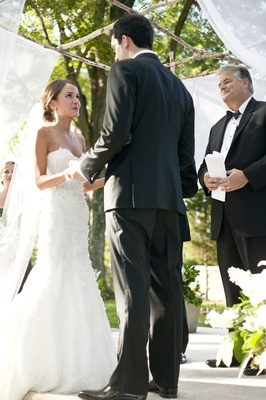 bride and groom say their vows I do under traditional jewish chuppah chuppa holding hands
