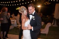 a newlywed bride and groom dance together under strings of lights on dance floor at night