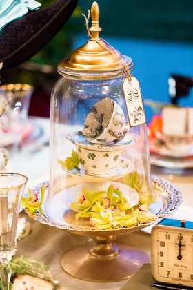 alice in wonderland wedding shoot, stack of teacups and green orchids under glass dome