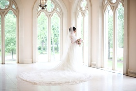 Bride in chateau wedding venue tall windows wedding dress cathedral train and veil