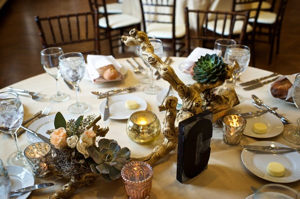 Round wedding table with rustic centerpiece featuring gold branch, succulent, antique color flowers