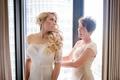 bride in off shoulder illusion wedding dress long blonde hair curls flower headpiece mother