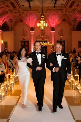 Groom in tuxedo walking with father and mother of groom in sparkly sequin white long dress