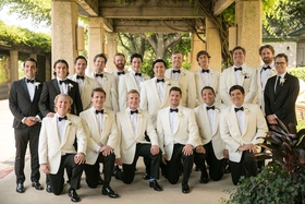 groom and groomsmen ivory white tuxedo jackets attendants in black white classic tuxedos