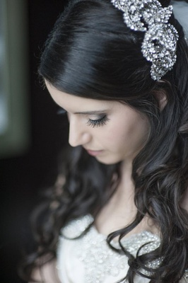 Bride with brown hair looks down with crystal headband