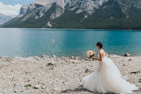 bride in watters mermaid wedding dress with beaded bodice low updo, lakeshore of Banff National Park