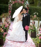 bride carrying parasol kisses groom on pink petal aisle