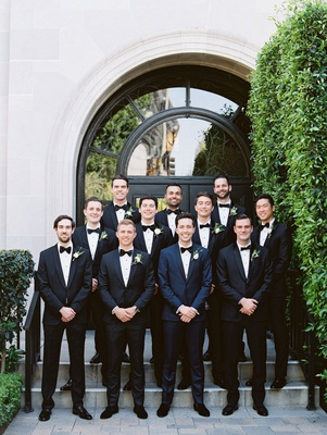 groom in navy tuxedo black bow tie with groomsmen in classic suits bow ties vibiana wedding venue la