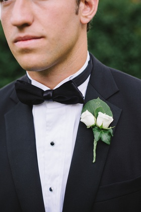 Groom in tuxedo wearing two small roses on lapel
