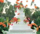 Five layer white wedding cake with edible tropical flowers