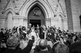 Black and white photo of bride and groom celebrating after wedding ceremony in cathedral