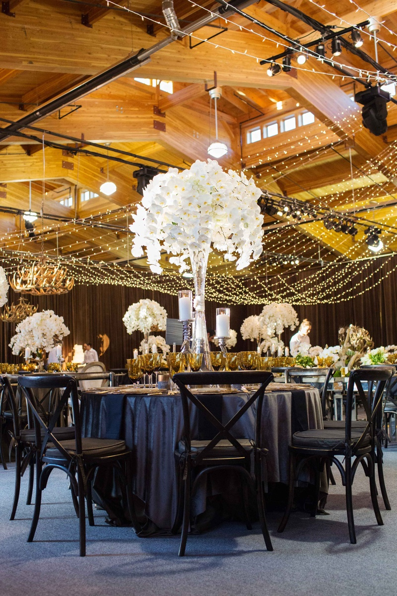 Aspen Colorado wedding reception in wood barn with dark linens chairs and tall white orchid flowers