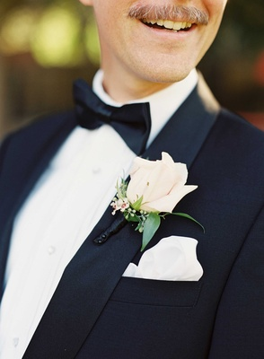 White and ivory rose bud boutonniere with green leaves wrapped in black ribbon for tuxedo groomsman