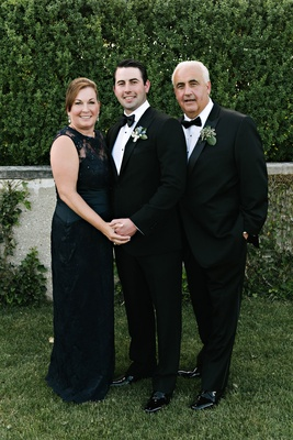 Mother of groom in sleeveless black long gown dress with lace neckline groom and father in tuxedos