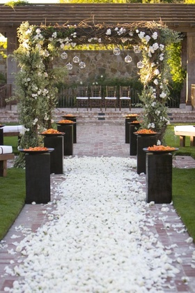 Brick aisle with white roses and rustic chuppah