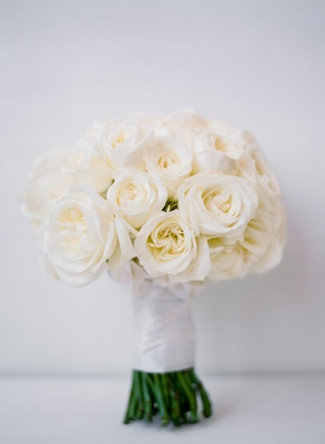bridal bouquet with ivory roses wrapped with a white ribbon