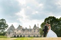 Bride and groom kiss in front of Oheka Castle
