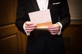groom in bonobos tux reads handwritten letter from bride