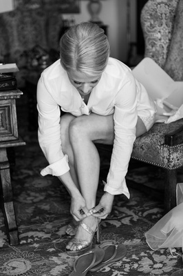 Black and white photo of bride putting on heels