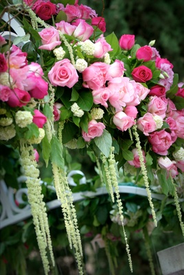 Pink roses and greenery arranged on wrought iron canopy