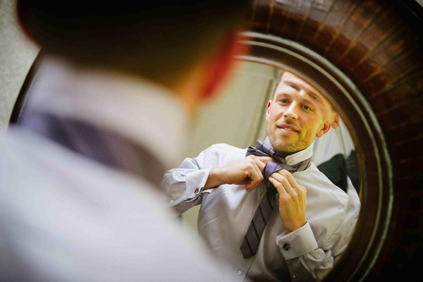 Scott Blokker putting on purple tie in mirror