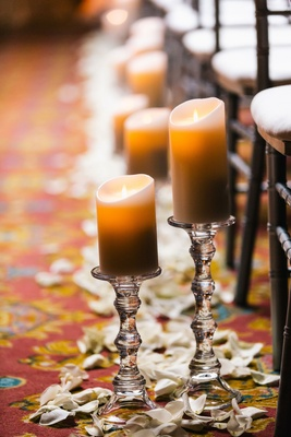 candles on stands with rose petals to line aisle for wedding ceremony