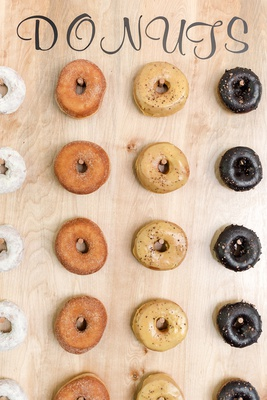 wedding dessert trend donut wall, donuts on wooden wall with pegs