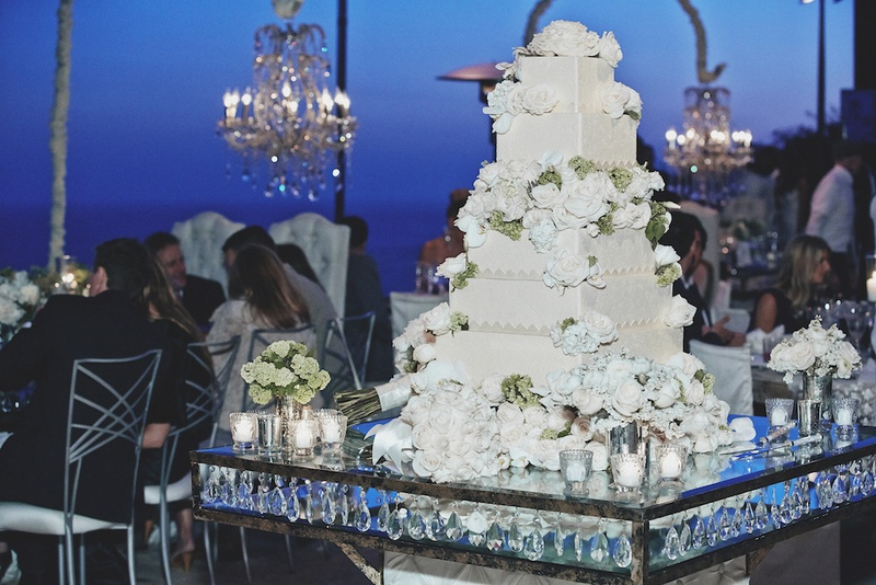 Square cake with sugar flowers on mirrored table