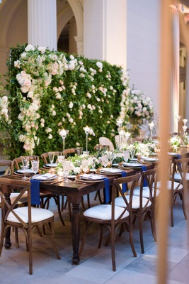 wedding reception greenery wall white pink flowers navy napkins wood vineyard chairs and table