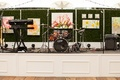 Drum set keyboard live band equipment at wedding reception on stage in front of green hedge wall