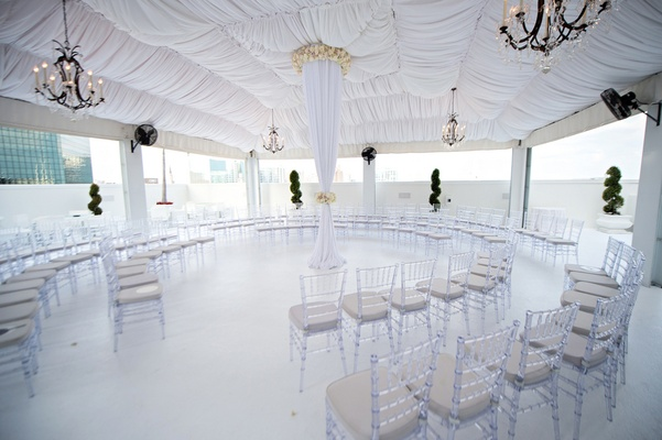 White tent and pillar surrounded by clear chairs