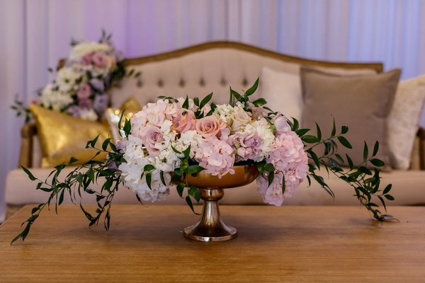 Wedding reception springtime decor lounge gold table purple flowers pillows centerpiece greenery