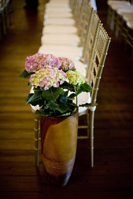 tall pot filled with pink hydrangeas at end of aisle