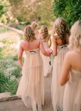 Bridesmaids walking down path in gowns